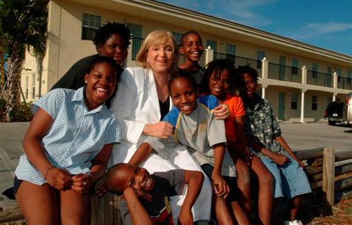 Patty Myura with children in front of Pat Reeves Village